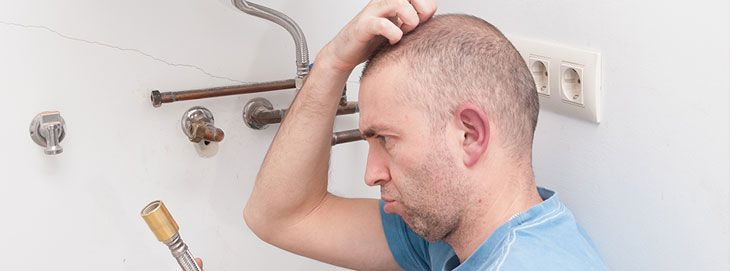 Man scratching head unable to complete plumbing